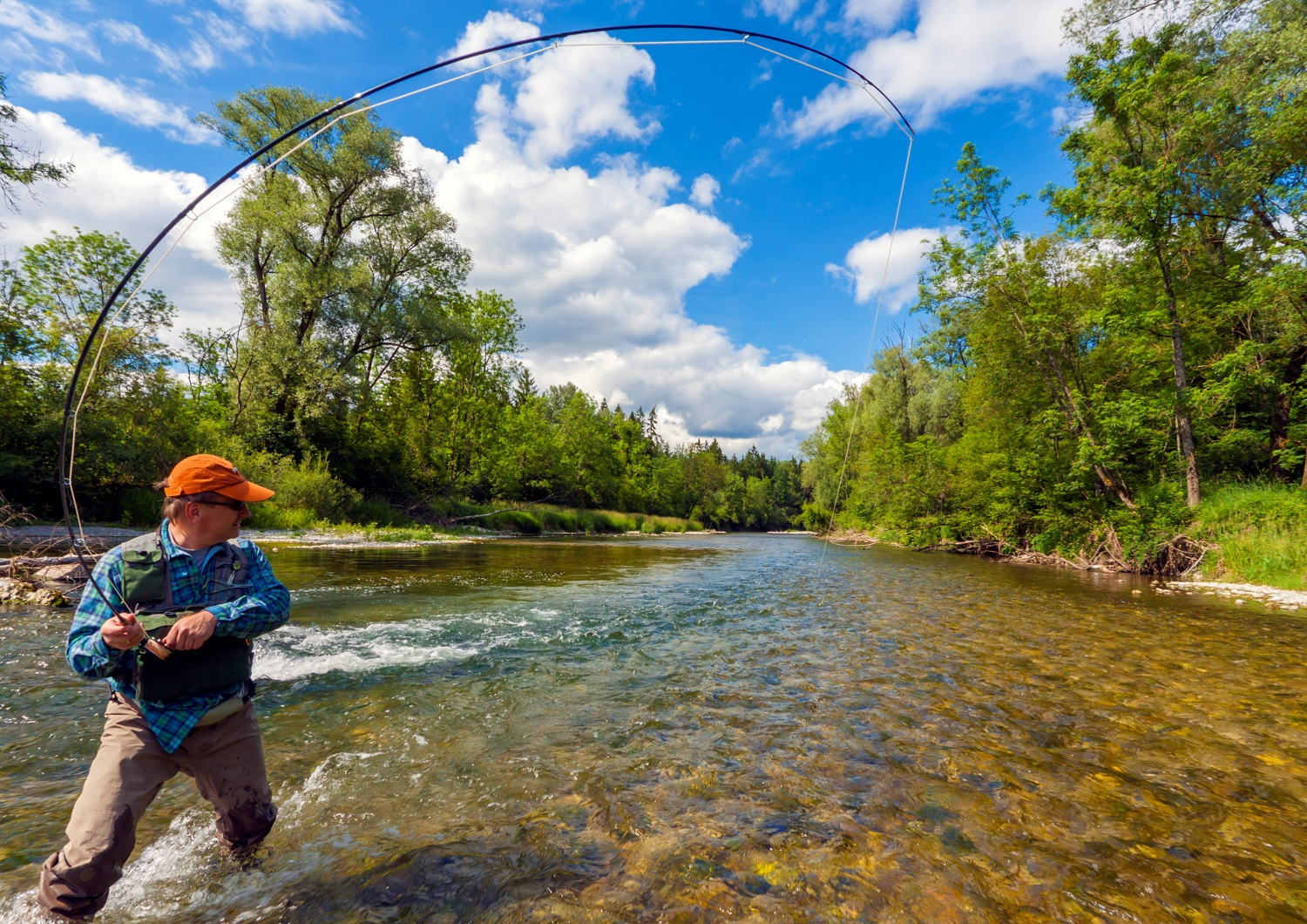 A fisherman is flyfishing in a beautiful River on a perfect Day.